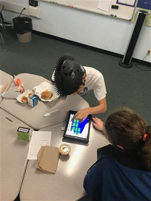 Peer and student using iPad app to talk about lunch
