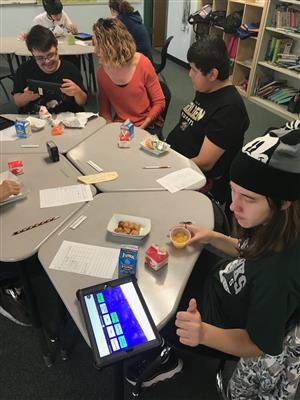 Teacher and three students eating lunch and communicating with iPad with communication app